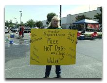 Woman holding a sign advertising hot dog sales