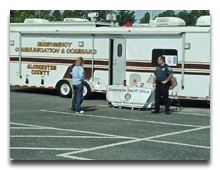 People standing by the Emergency Management Trailer
