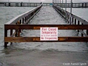 Flooded pier with a closed temporarily sign
