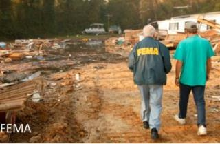 FEMA worker and man walking through destruction caused by hurricane Isabel